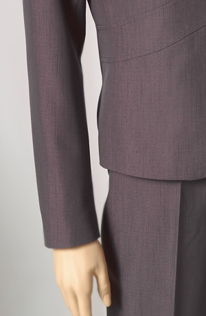 Elegantní kalhotový kostým se zdobenými klopami.