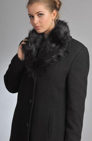 Dlouhý dámský černý kabát s kožešinou kolem límce.