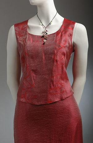 Dámský společenský trojkomplet. Krátký vzorovaný kabátek, top a sukně je kombinovaná ze dvou materiálů, uni a vzorovaný materiál, úzká sukně s volánem v lady délce