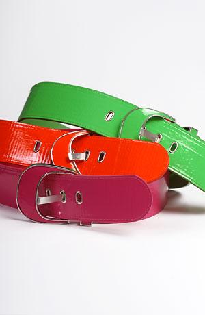 Módní oděvní doplňky - dámské pásky s velkou sponou v módních barvách zelené, oranžové a fialové.