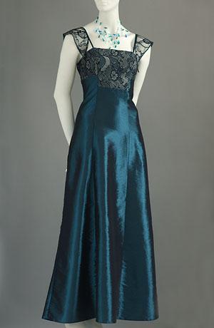 Dlouhé šaty z lesklého taftu s krajkový zdobením.