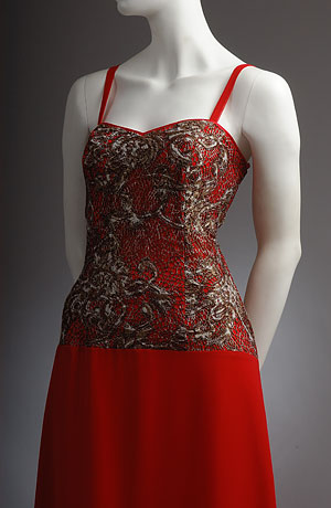 Červené korzetové šaty s prodlouženým živůtkem potaženým krajkou, mírně rozšířená sukně, sedlo lemované stuhou. Zapínání vzadu na zip.