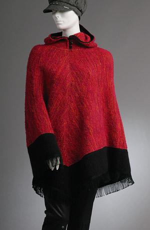 Pletené pončo s kapucí a černým lemem s třásněmi.