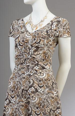 Letní šaty s řasením v partii břicha mají široký výstřih ve tvaru V na předním i zadním díle.Malé rukávky bez nabírání působí mladistvě i u větších velikostí.Sukně v lady délce je mírně rozšířená.