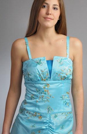 Taftové plesové šaty se zvýrazněným vysokým pasem korzetového střihu mají nabírané sedlo a náběry na předním dílu sukně,které jsou nad vysokým rozparkem zdobeným řasenou organzou. Zlatá výšivka motýlků a květů má nádech asi