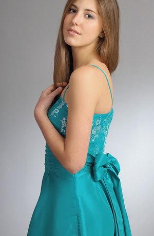 Korzetové šaty zdobené jemným krajkovým tylem se stříbrným potiskem mají vzadu velkou módní mašli.Taftová kolová sukně je ještě i nabíraná,aby zdůraznila svou bohatost.