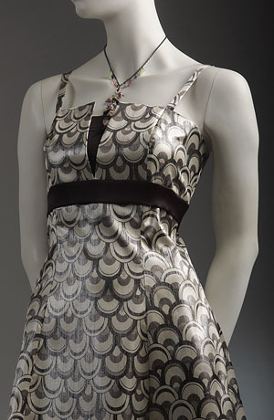 Krátké společenské šaty na ramínka s rozšířenou sukní zdobenou stuhou a tylem, sedlo s průstřihem podloženým elastickým saténem, který je použit i na stuhu pod prsy a podložení pod šněrováním.