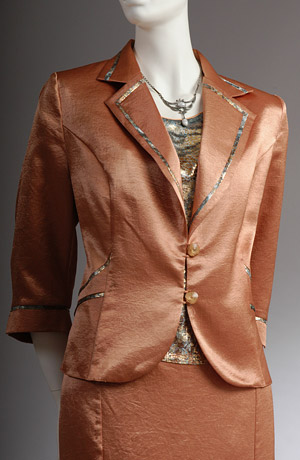 Dámský kostýmek se zdobeným sakem s lesklým lemováním.