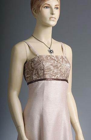 Ramínkové svatební šaty do sedýlka zdobeného elastickou krajkou. Přiléhavý živůtek přechází v rozšířenou sukni v linii A. Pod prsy je flitrová porta. Celé šaty jsou v barvě bílé kávy. Zapínání vzadu na šněrování.