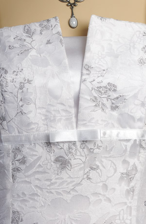 Svatební šaty na ramínka jsou vyrobeny z mačkaného materiálu se stříbrným potiskem květů.Jsou podloženy elastickým bílým saténem,který prosvítá v transparentním vzoru a dodává tak šatům luxusní vzhled.Spodnička je zdobena tylem